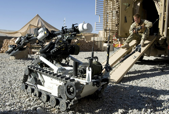 A soldier operates the remote controlled Mark 8 Wheel Barrow Counter IED Robot. The soldier is part of the EOD (Explosive Ordinance Device) and Search team based out of FOB (Forward Operating Base) Ouellette. Courtesy of the UK Ministry of Defense.